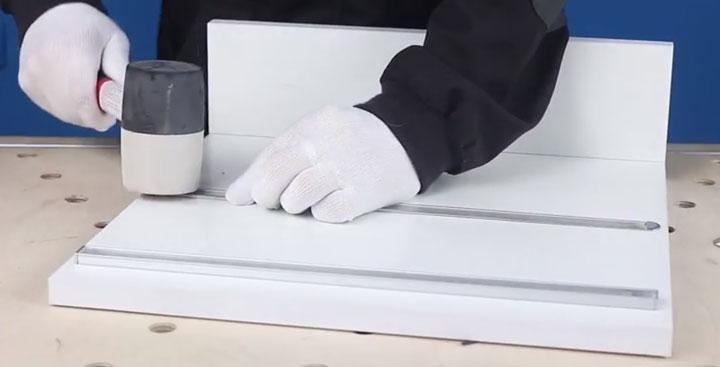 установка врезного профиля в паз при помощи резинового молотка