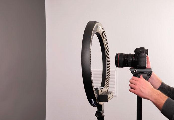 штатив с камерой позади кольцевого света